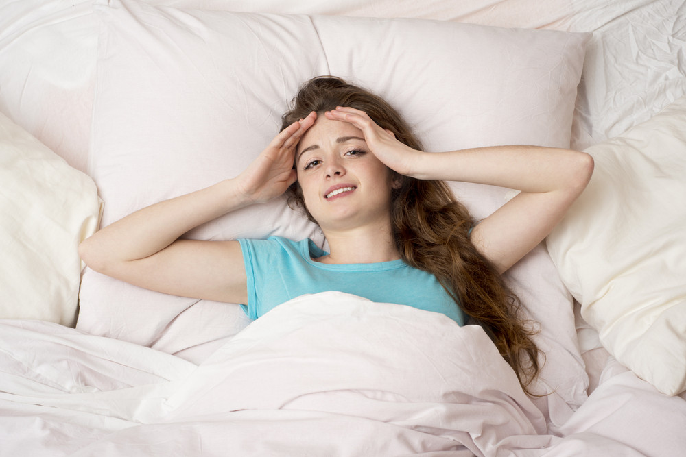 Sick woman with headache is lying in bed
