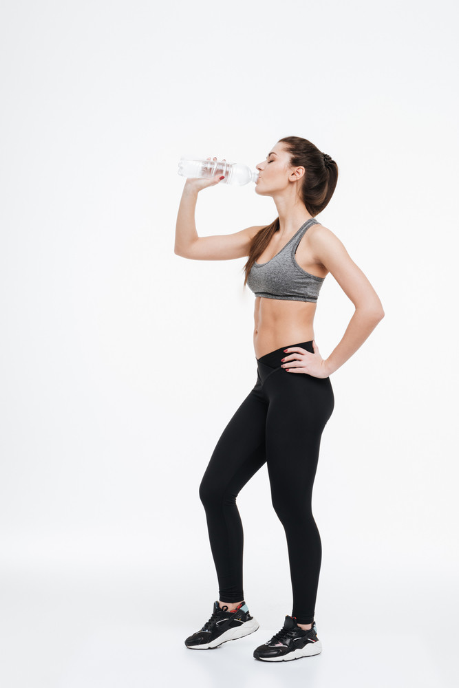 Side view full length portrait of a young healthy sports woman drinking from a water bottle isolated on a white background