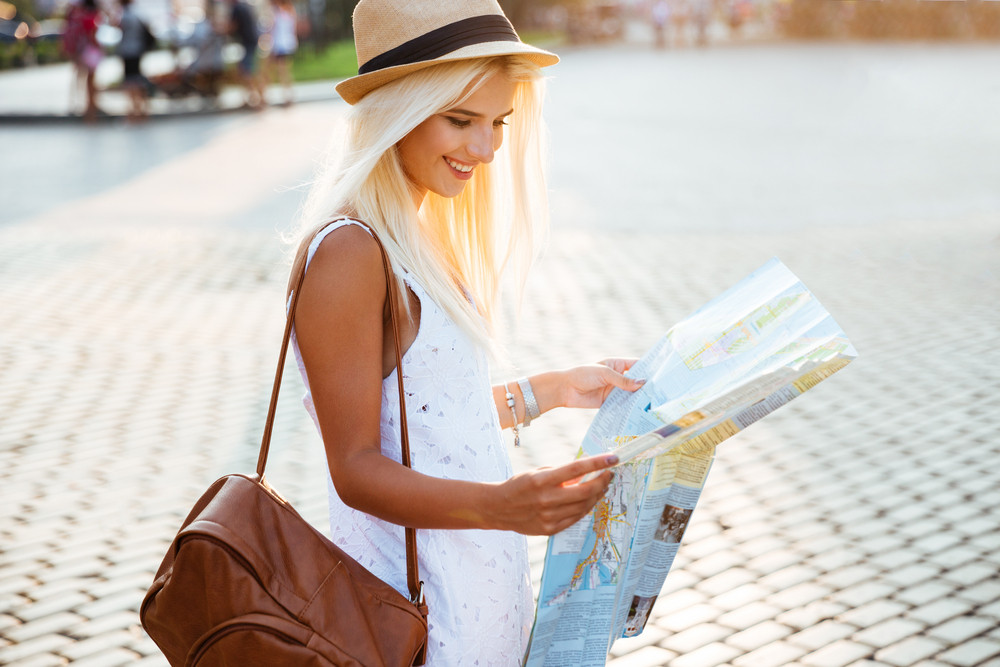 Side view of a happy tourist woman on vacation with map visiting city
