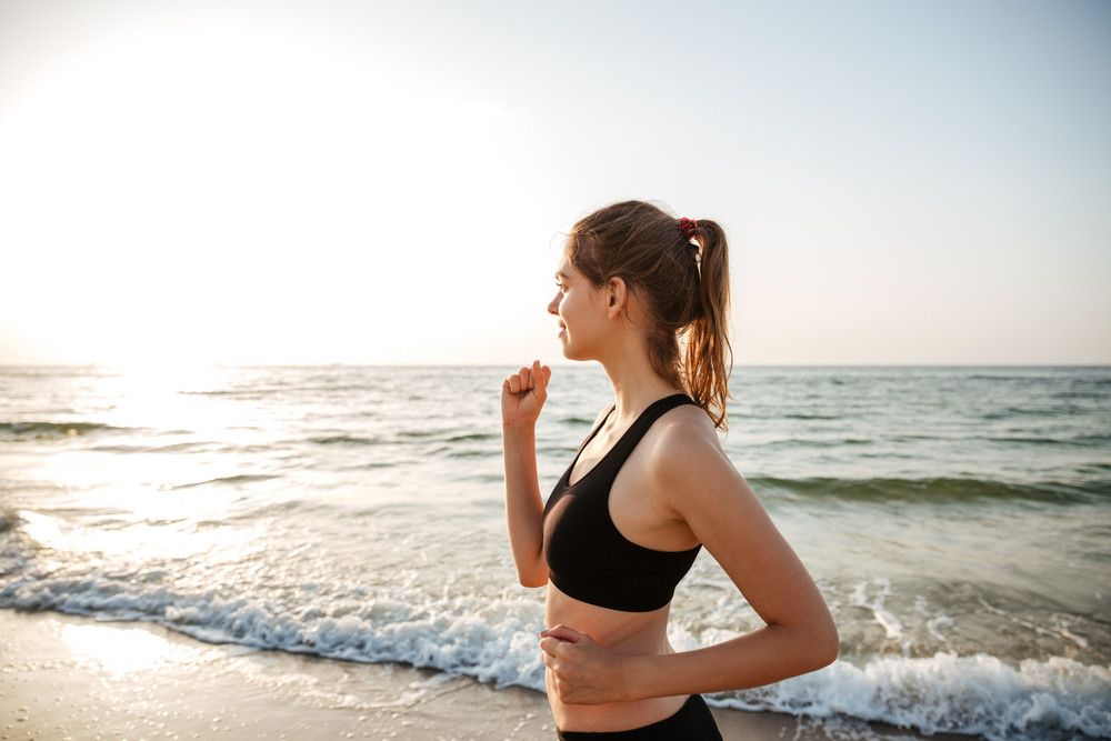Side view of a healthy young woman running on beach outdoors