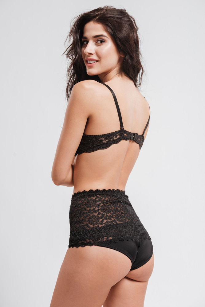 Side view of a smiling attractive woman in lingerie looking over her shoulder at camera isolated on a white background
