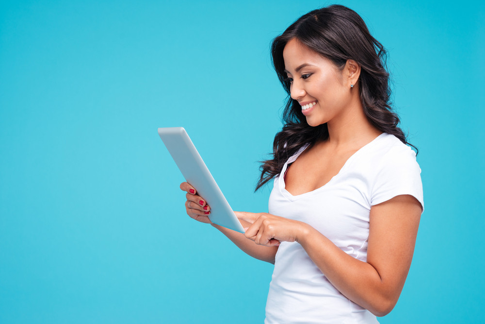 Side view of a smiling young woman using tablet computer isolated on a blue background