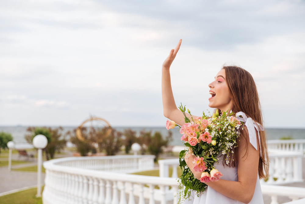 Side view of a young girl holding flowers and waving outdoors at the white terrace