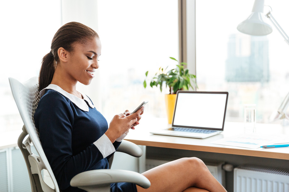 Side view of African business lady sitting by the table with phone