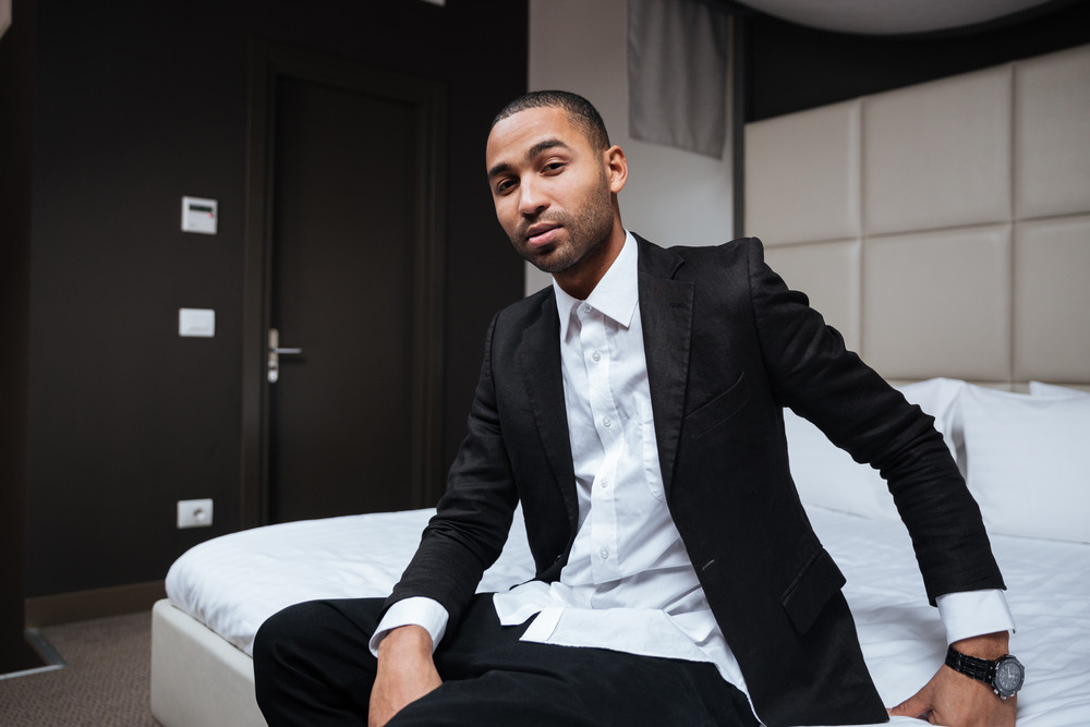Side view of African man in suit sitting on bed in hotel room and looking at camera