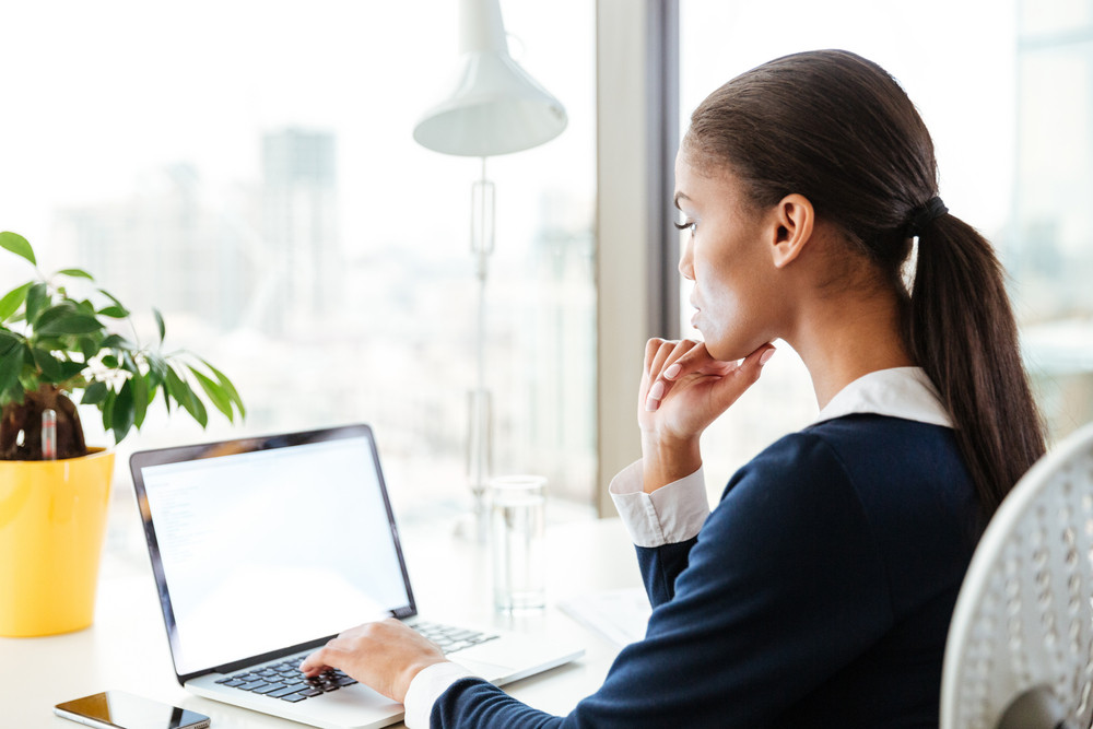 Side view of afro business woman in dress sitting by the table near the window and using laptop in office