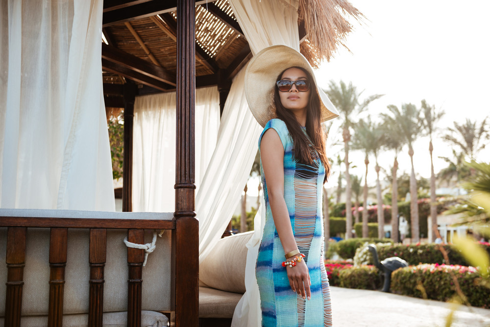 Side view of Brunette woman in beachwear and sunglases which posing near the alcove and looking away