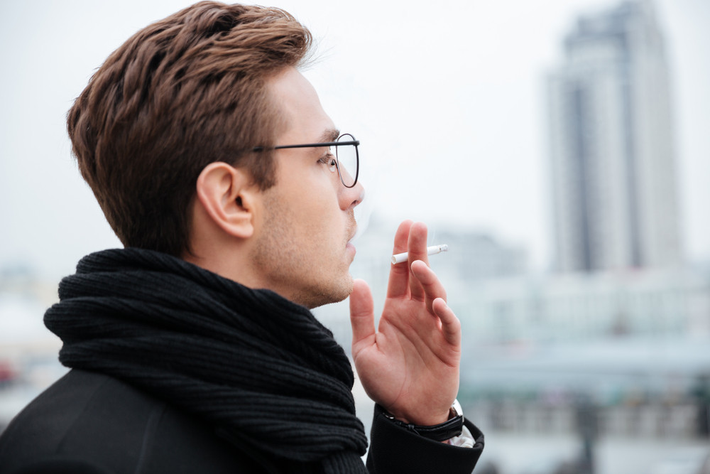 Side view of business man in glasses and warm clothes smoking cigarette on the street
