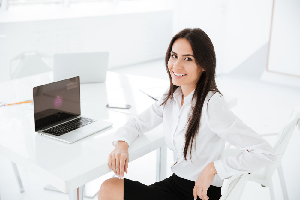 Side view of business woman sitting by the table in office and looking at camera. Top view