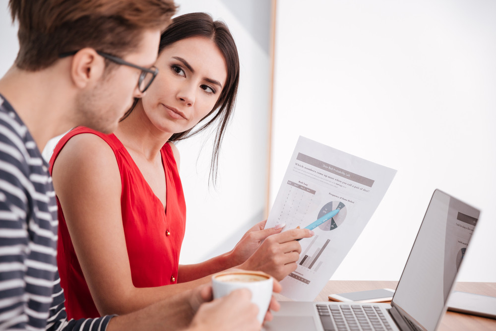 Side view of couple sitting by the table with laptop and documents in office