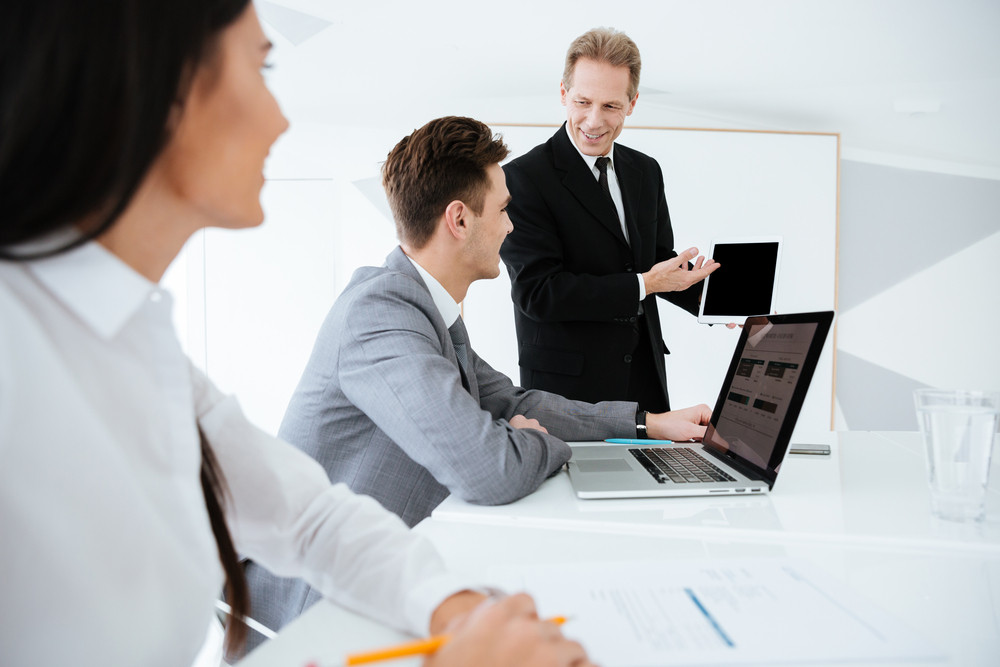 Side view of Elderly smiling business man showing blank tablet computer screen to his colleagues on conference