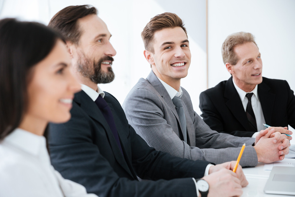 Side view of Happy Business people sit by the table in office and one man looking at camera