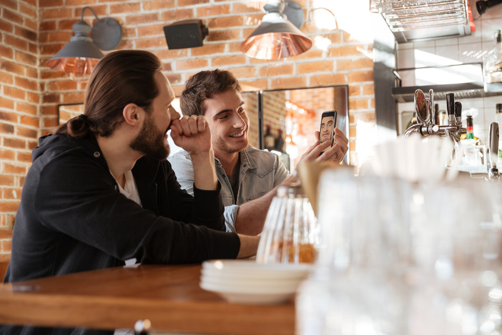 Side view of Happy Friends standing near the bar and one man showing photo on phone
