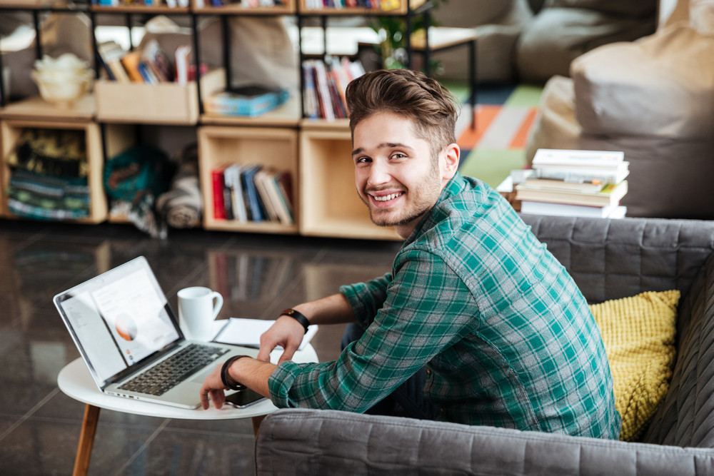 Side view of man in green shirt sitting on sofa by the table with laptop and looking at camera. Coworking