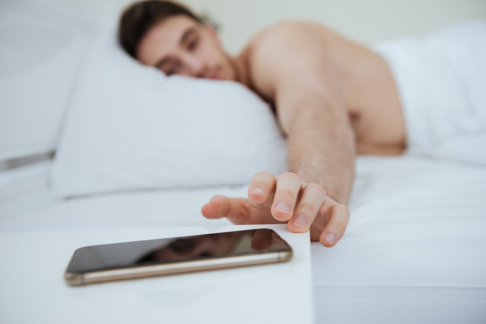 Side view of man lying on bed. Focus on phone which lying near the bed