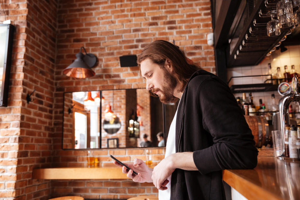 Side view of man standing on bar with phone in cafe