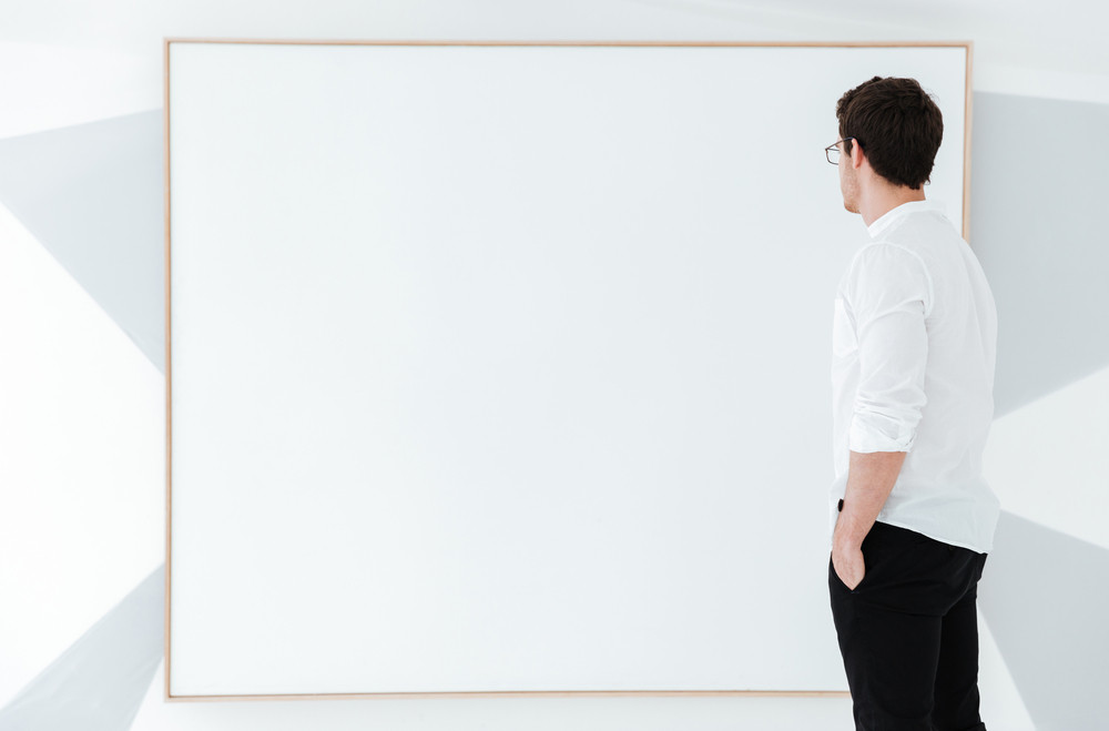 Side view of man wearing eyeglasses and dressed in white shirt standing near big board.