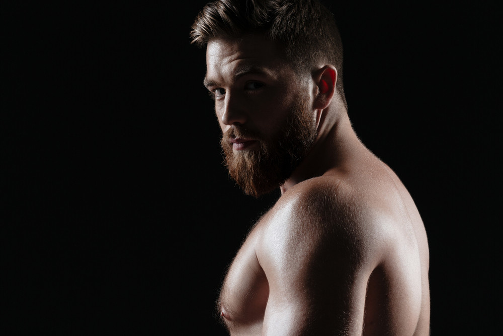 Side view of naked strong man. isolated dark background