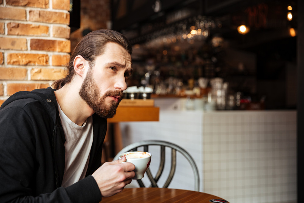 Side view of Serious Bearded man sitting by the table in cafe with cup of coffee and looking away