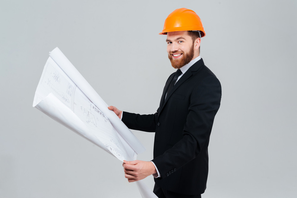 Side view of smiling bearded engineer in suit and orange helmet with open layout looking at camera. Isolated gray background