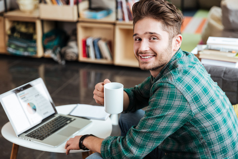 Side view of smiling man in green shirt sitting on sofa by the table with laptop and looking at camera. Coworking