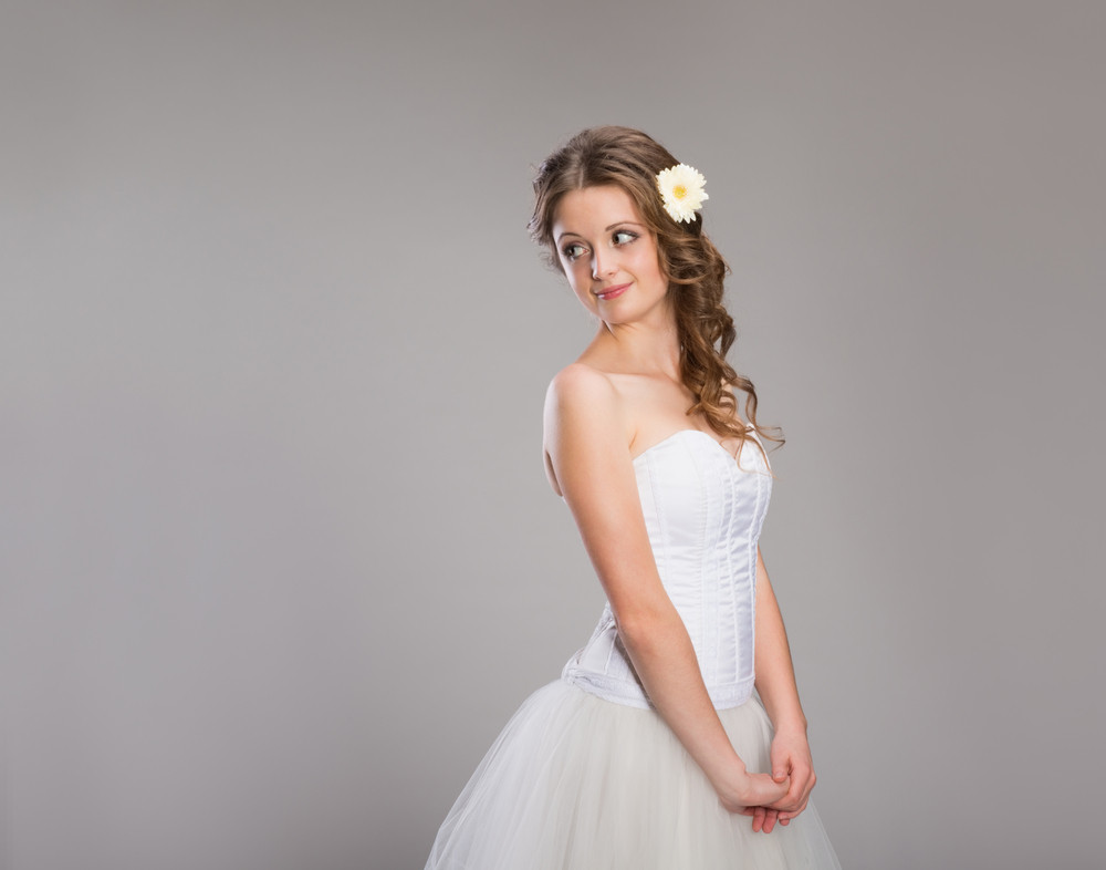 Side view of young bride with hand on chin standing over gray background
