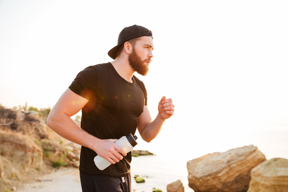 Side view portrait of a bearded sports man running outdoors near sea