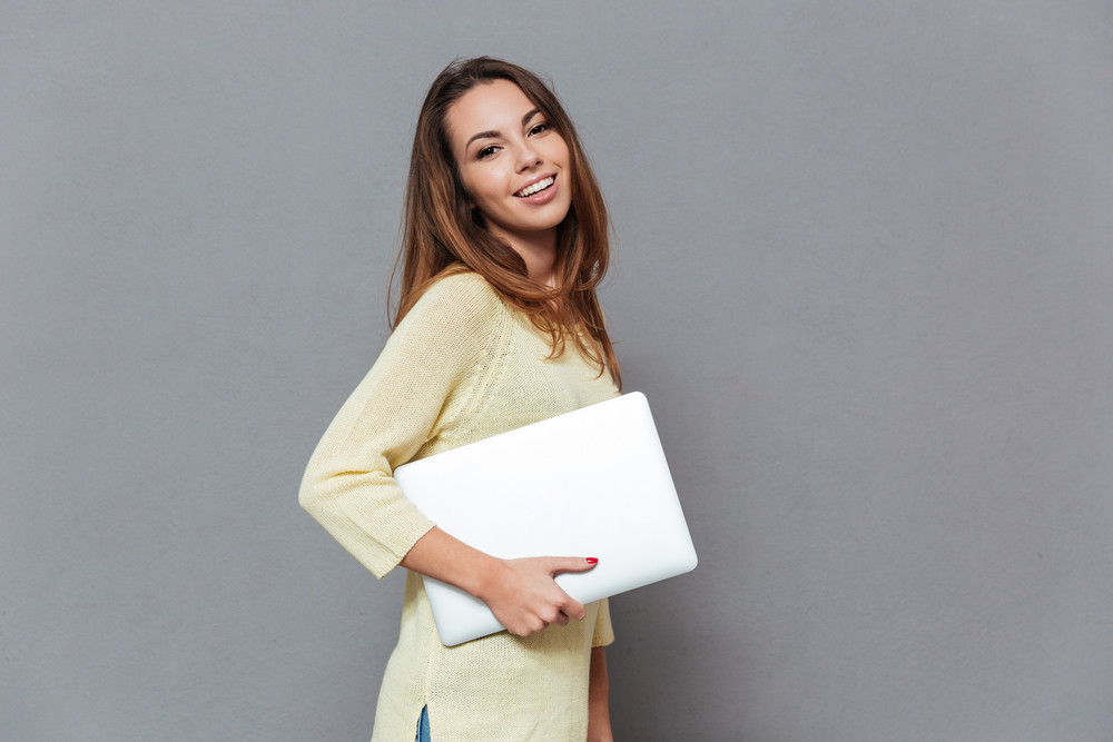 Side view portrait of a smiling brunette woman standing and holding laptop isolated on the gray background