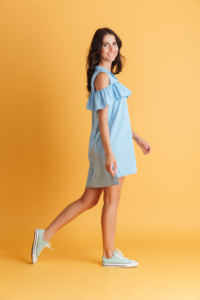 Side view portrait of a young smiling brunette woman in blue dress posing over orange background