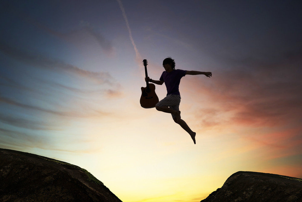 silhouette of brave guy holding the guitar jumping  through the gap,inspiration and success concept.