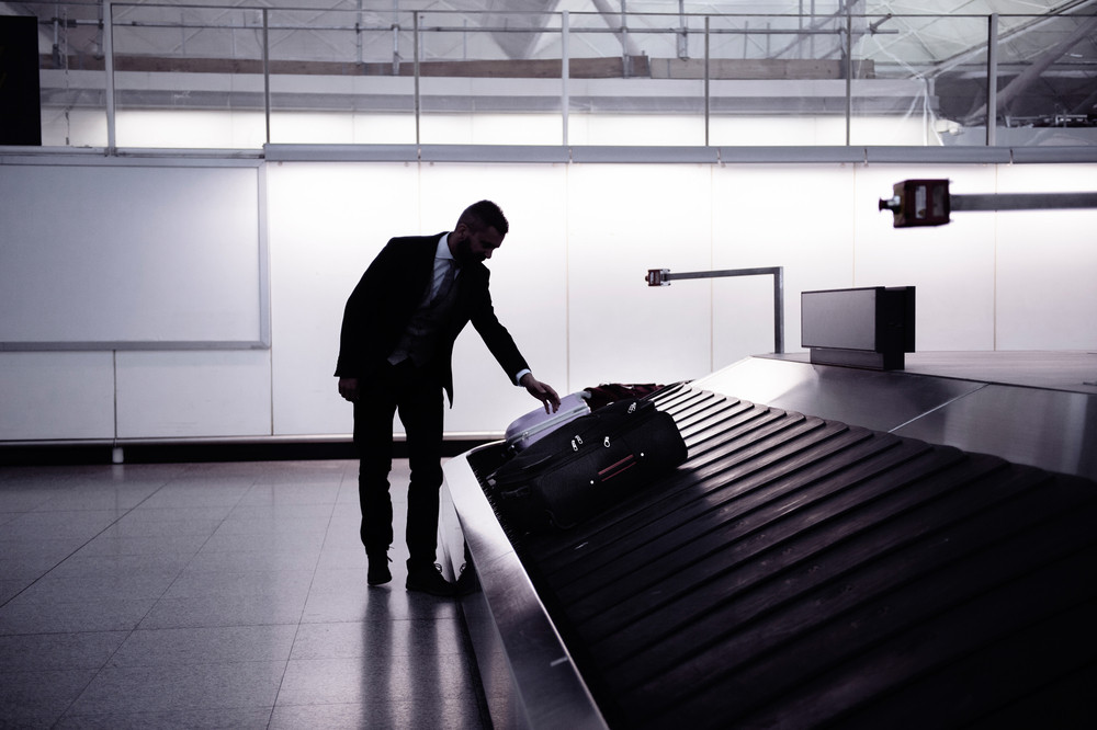 Silhouette of businessman picking up suitcase on luggage conveyor belt at the airport
