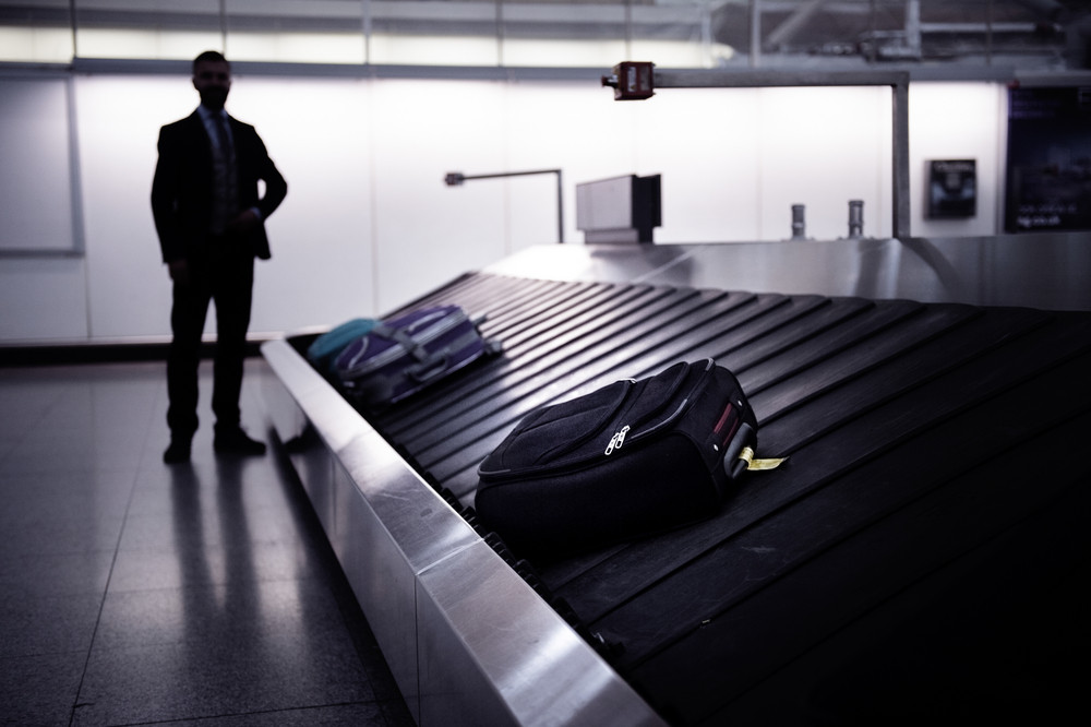 Silhouette of businessman waiting for suitcase on luggage conveyor belt at the airport