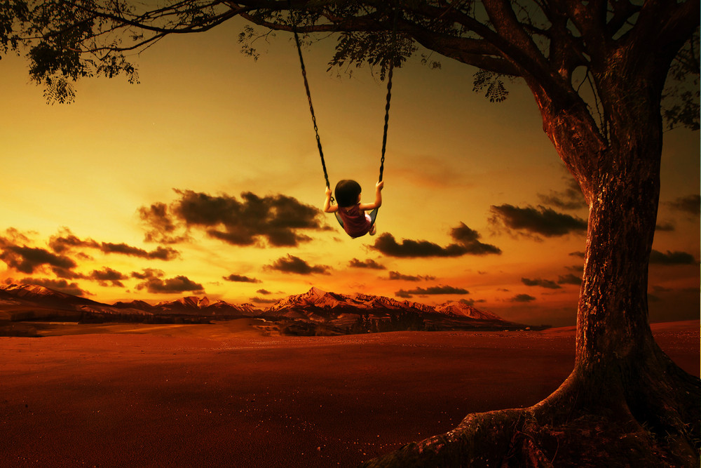 silhouette of happy little girl on a swing with sunset background