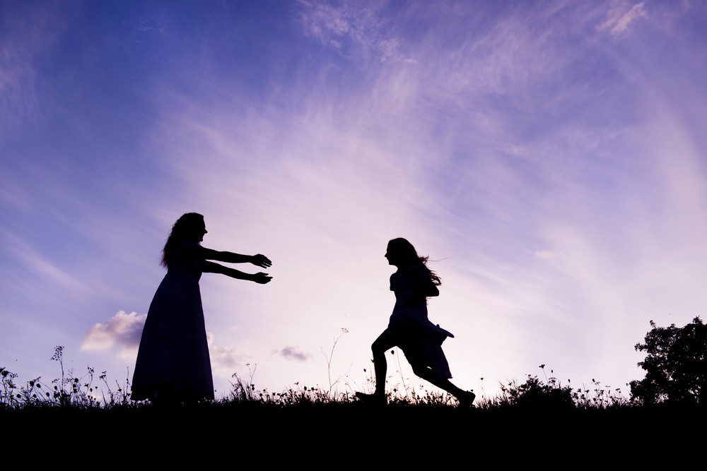 Silhouette of happy mother having fun with her daughter