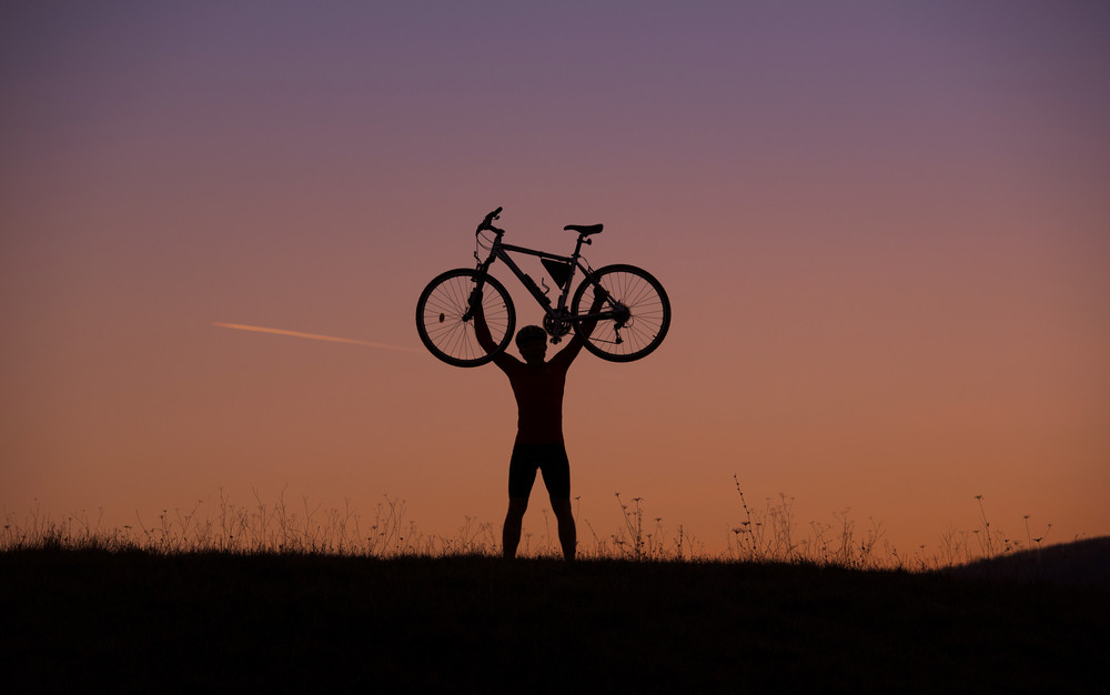Silhouette of mountain biker holding his bike in sunset on the meadow