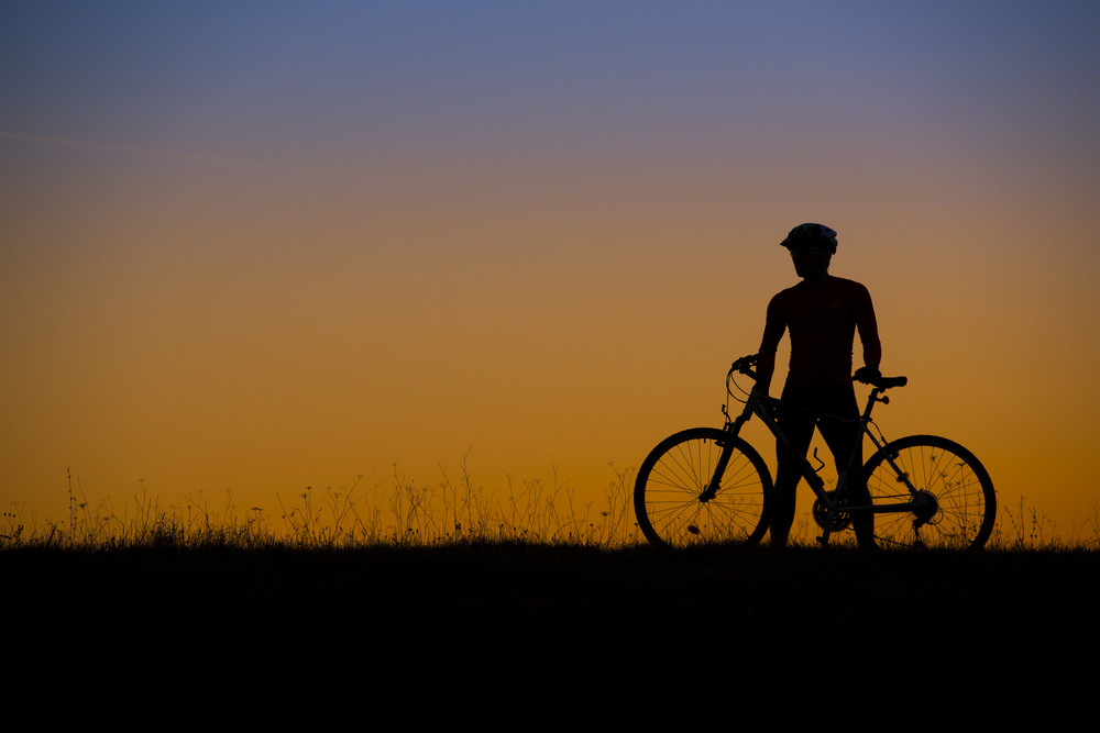silhouette of mountain biker in sunset on the meadow