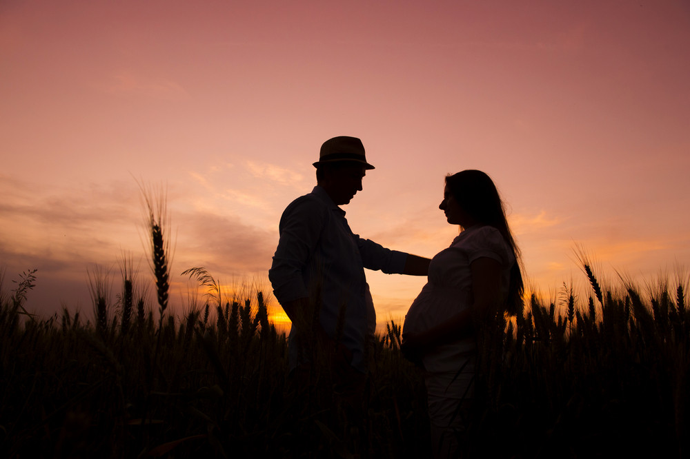 Silhouette of pregnant couple in the sunset