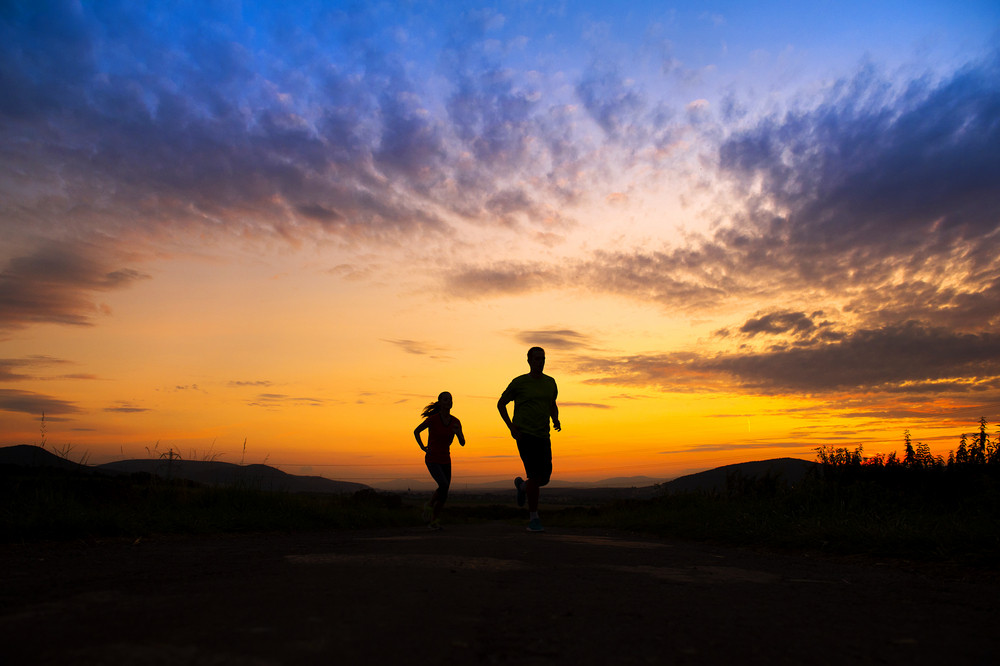 Silhouette of young couple running in sunset