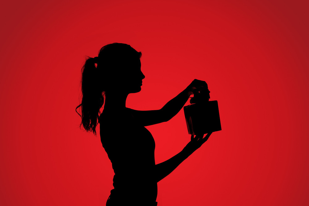 Silhouette of young woman with gift over red background