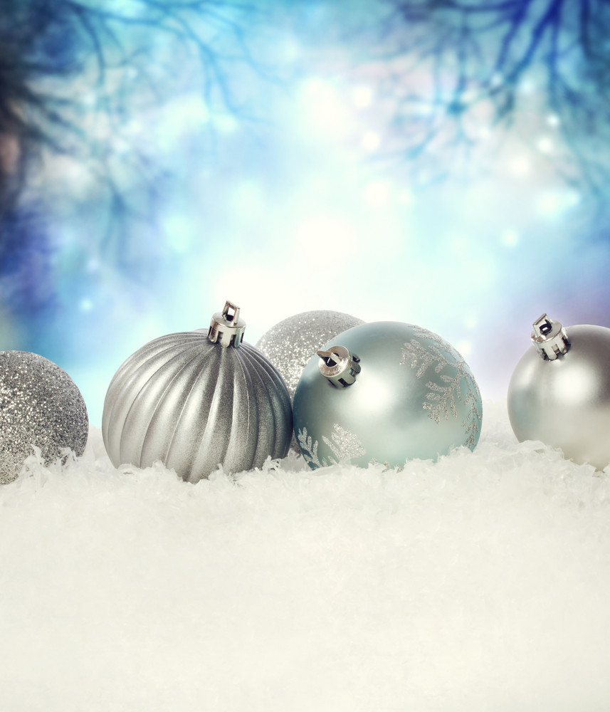 Silver Christmas baubles on the snow in the night
