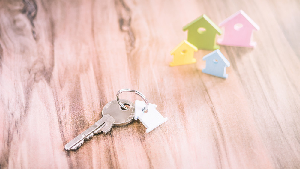 Silver Key with Breloque in Form of House and some Miniature Symbol of Houses on Side in Different Colours on Wooden Surface