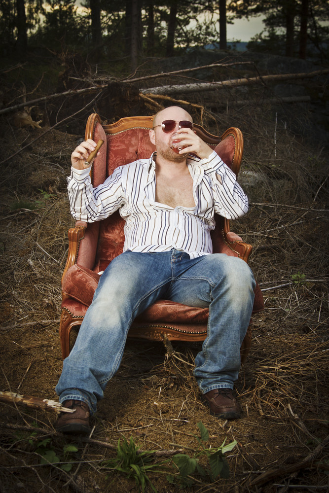 Sleazy man / dude in a classic vintage chair in the middle of a logging area. Smoke a cigar and drinking Cognac in woods.