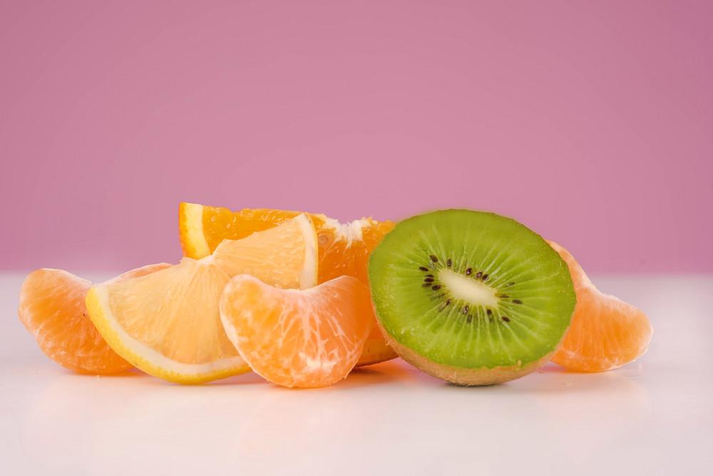 Sliced fresh peeled kiwi, lemon, tangerine and orange on a table isolated on a pink background