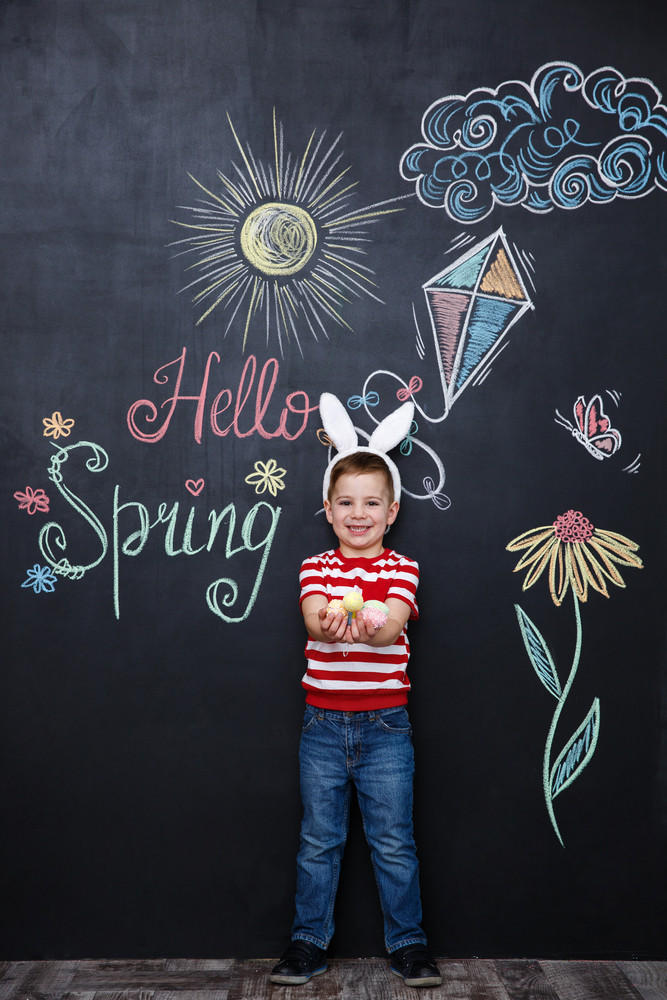 Small little kid wearing bunny ears and holding bunch of easter eggs over chalk board with colorful text background