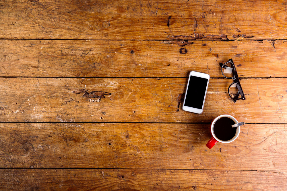 Smartphone, cup of coffee and eyeglasses laid on old office desk, flat lay, copy space.