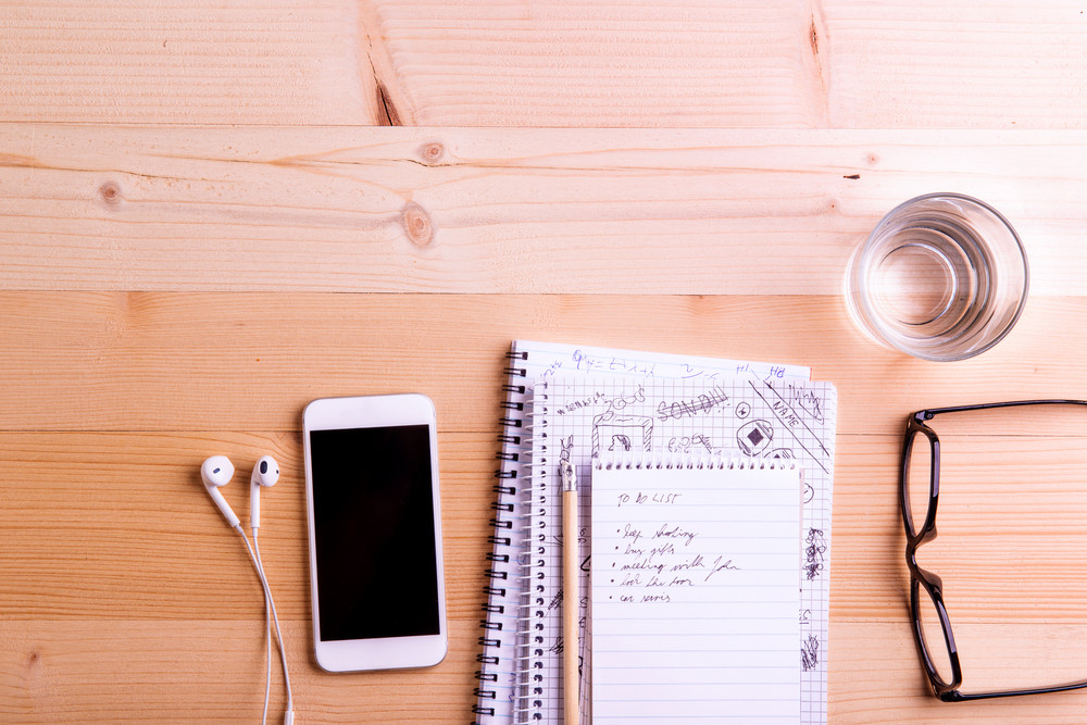 スマートフォン、イヤホン、水ガラス、眼鏡がオフィスデスクに置かれています。ガジェットや事務用品を備えたデスク。木製の背景に撮影されたスタジオ。フラットレイ、空のコピースペース。