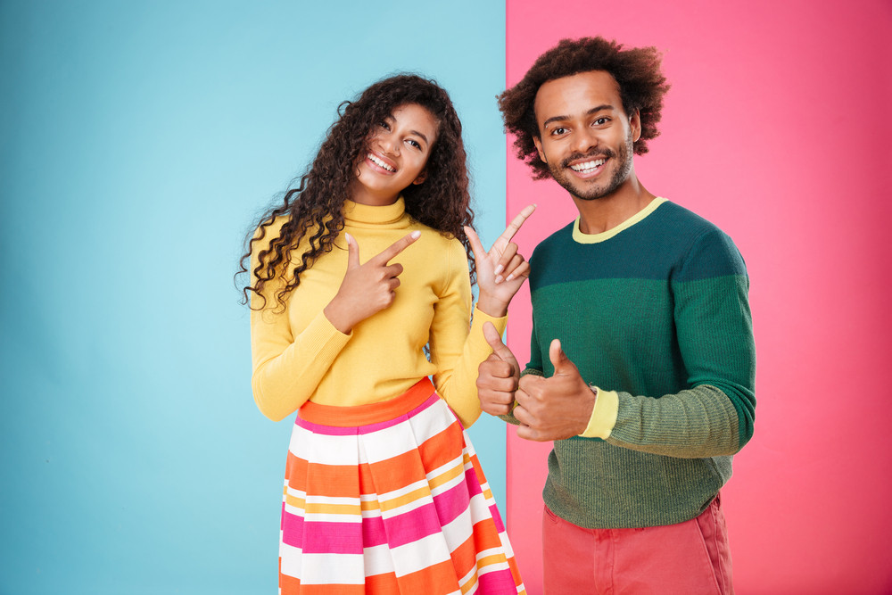 Smiling african american young couple showing thumbs up over colorful background