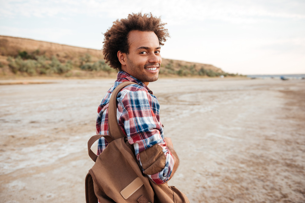 Smiling african american young man with backpack walking on the beach