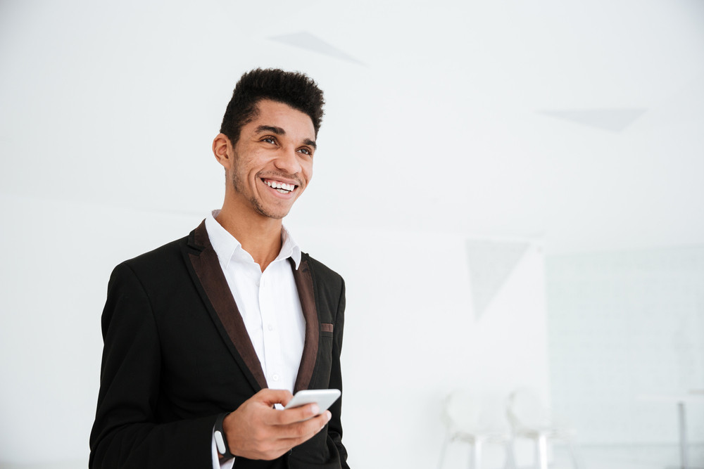 Smiling african business man in black suit holding phone in hand standing in office and looking aside