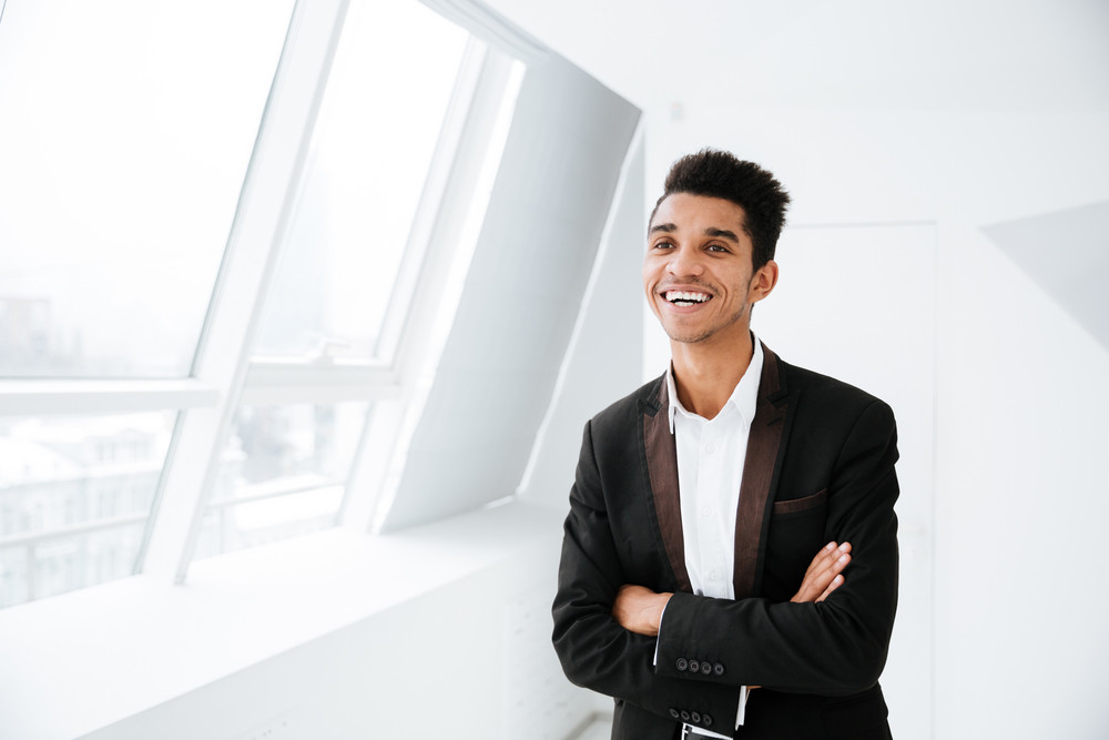 Smiling African business man in black suit standing near the window in office with arms crossed and looking aside